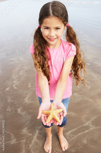 Girl Holding Starfish Found On Beach