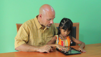 Asian Girl Learns How To Use Tablet With Father