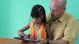 Father And Daughter Playing Game On Digital Tablet