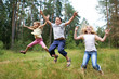 Children jump on lawn in summer forest