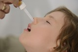 Congested nose: Mom applying nose drops poster