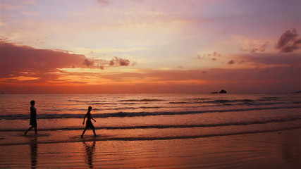 Mother and son go on the seashore on a sunset. Phuket.