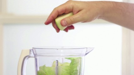 Close up of hand inserting fruits and vegetables into a blender
