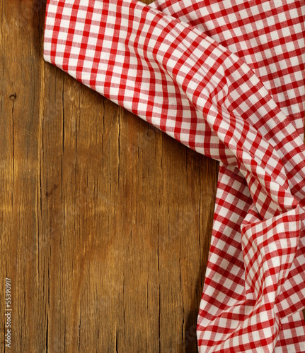 Wooden background with red checkered kitchen towel