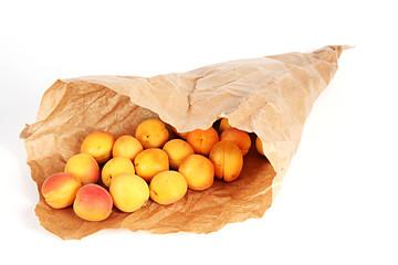 Aprikosen in der Papiertüte auf weiß isoliert