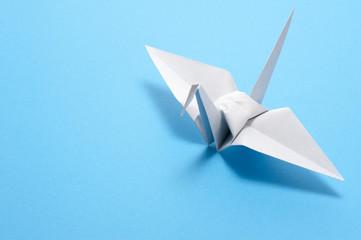 水色の背景に白色の折り鶴