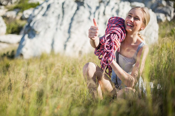 Smiling woman holding climbing equipment crouching down