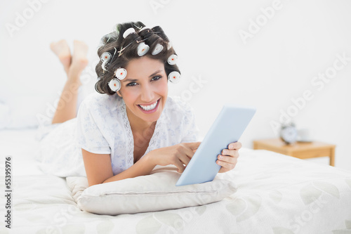 Smiling brunette in hair rollers lying on her bed using her tabl