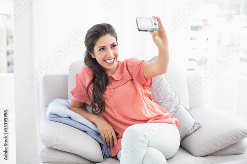Pretty brunette sitting on her sofa taking a picture of herself