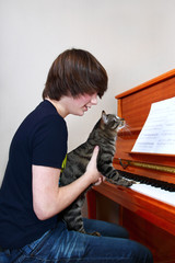 Boy and cat play piano