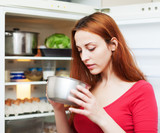 woman looking for something in pan near fridge