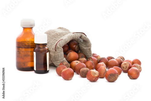Hazelnuts in bag and bottles with oil.