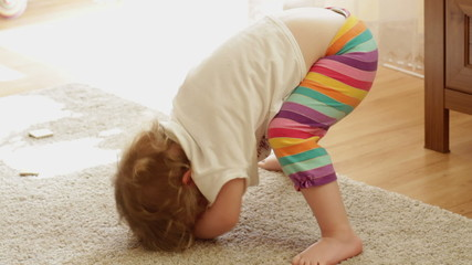 A cute little girl is bending over on floor
