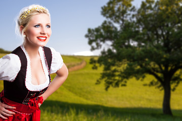 junge Frau im Dirndl vor ländlichem Hintergrund