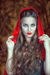 Beautiful halloween woman in red cloak