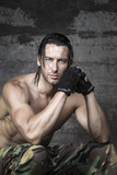 portrait of handsome muscle athlete on wall background