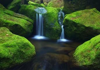 Cascade on small mountain stream, water over basalt boulders.