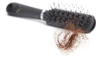 Hair loss concept: hair ball and hairbrush, isolated on white