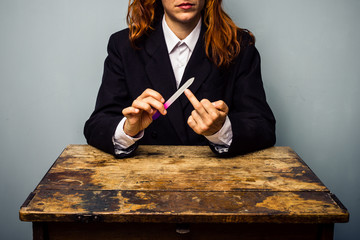 Businesswoman displaying obscene gesture while filing her nails