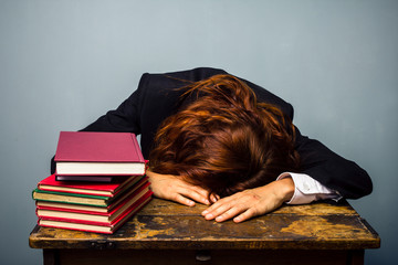 Businesswoman sleeping next to stack of books