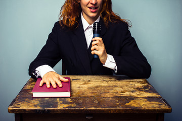 Woman in suit talking about book