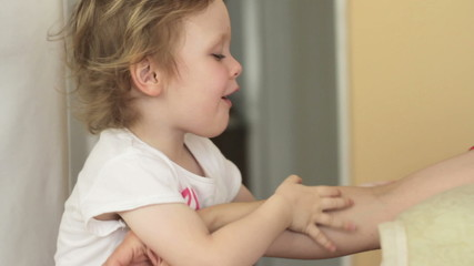 Little girl tickles her mother's hand