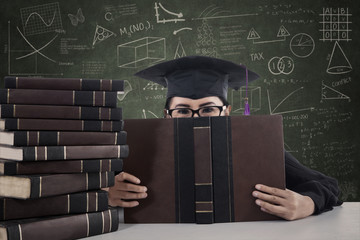 Asian female graduate peeking from behind a book