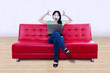 Stressful female with laptop sit on red sofa