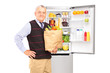 Mature gentleman holding a paper bag in front of fridge