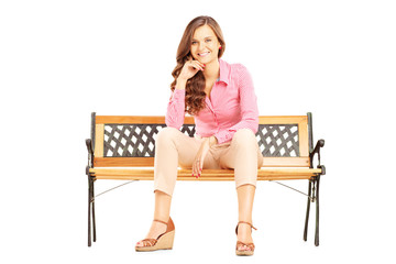Beautiful smiling woman sitting on a bench and looking at camera
