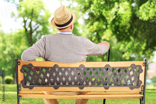 Mature man resting on a bench in a park