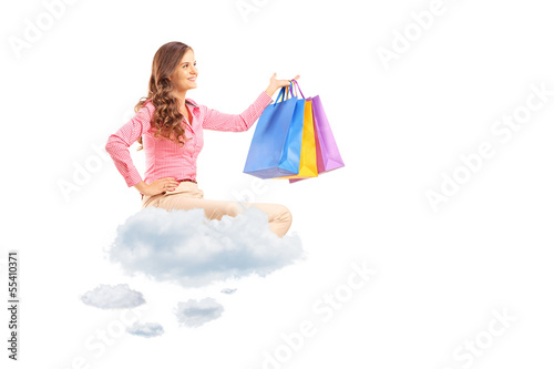 Young female flying on clouds and holding shopping bags