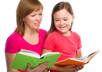 Mother and her daughter are reading books
