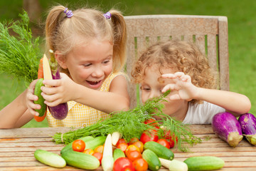 Two happy little kids with vegetables . Concept of healthy food.