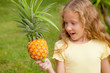 happy little girl holding in hands  a pineapple
