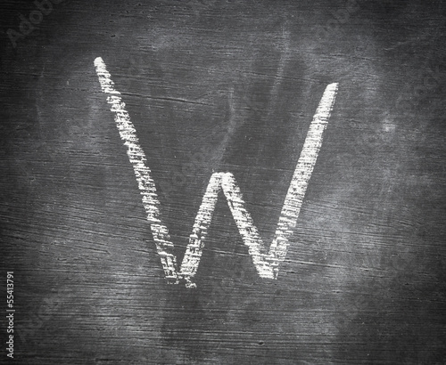 W - letter written on black chalkboard.