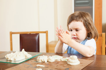 The child makes dough figurines