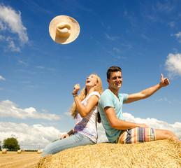 Ausgelassenheit: Glückliche Menschen im Sommer auf Strohballen