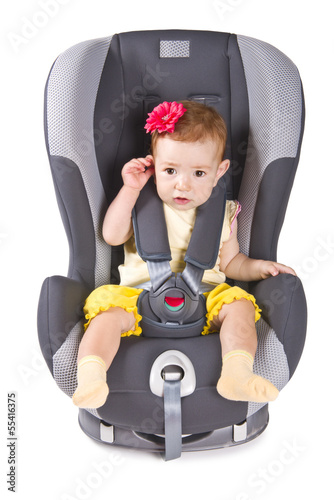 Cute child sitting in a car seat, isolated on white