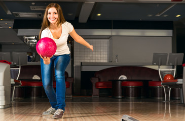 pleasant young woman throws a bowling ball