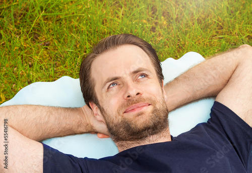 Happy man laying on grass and looking up