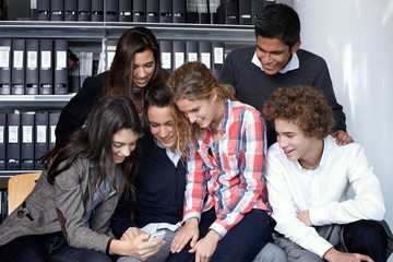 Group of teenagers looking pictures with smart phone