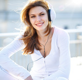 Captivating young woman listens to music through headphones