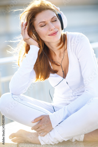Joyous young woman listens to music through headphones