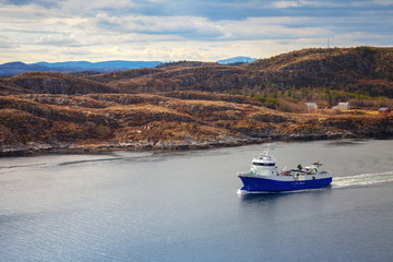 Blue Norwegian fish carrier ship in the fjord