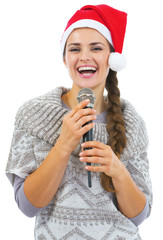 Smiling young woman in sweater and christmas hat with microphone