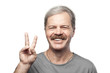 smiling mature man showing victory sign isolated on white backgr