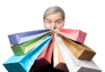 surprised mature man holding shopping bags near face isolated on