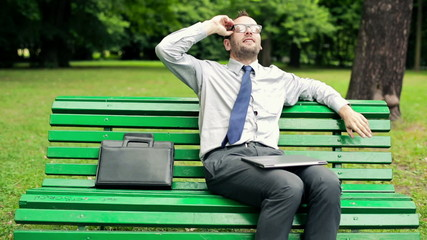 Businessman finishing working on laptop in the park