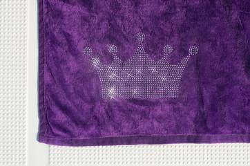 Crown of shiny rhinestone on a beach towel